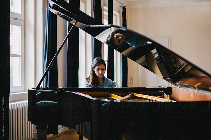 Brunette woman playing piano indoor by VeaVea for Stocksy United