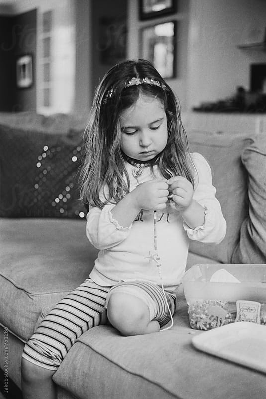 Cute young girl sitting on a couch making a necklace by Jakob for Stocksy United