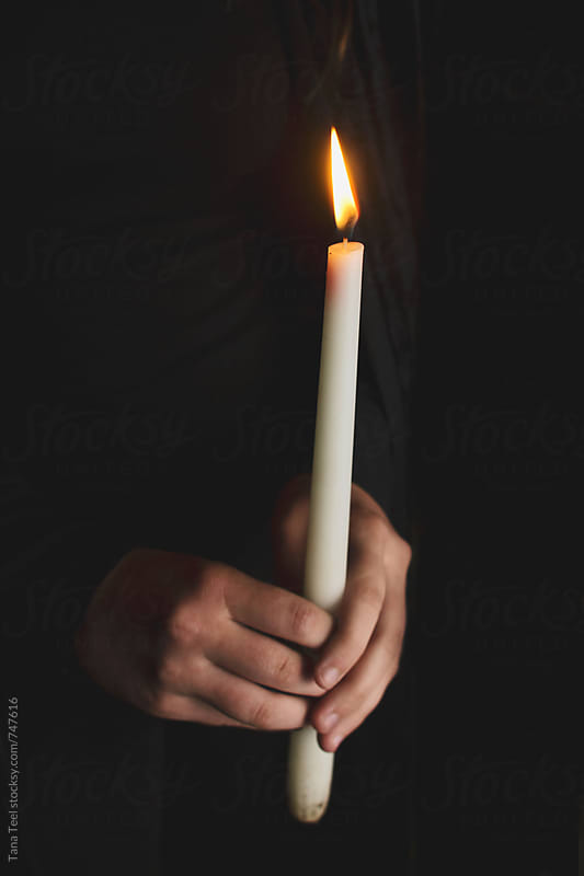 hands hold lit candle in the dark by Tana Teel for Stocksy United