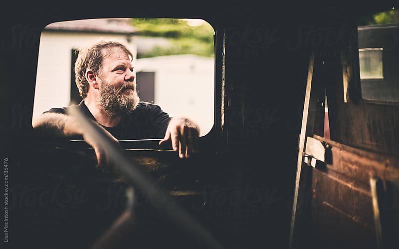 bearded man looking inside window of vintage truck by Lisa MacIntosh for Stocksy United