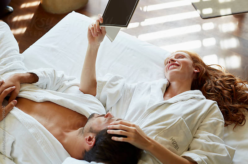 Woman Reading Book For Man While Lying In Bed by ALTO IMAGES for Stocksy United