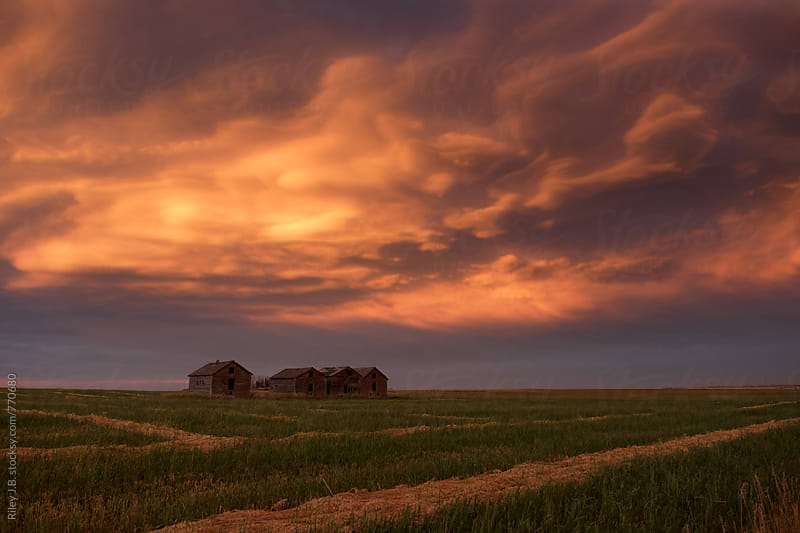 Beautiful clouds over a farm at sunset by Riley Joseph for Stocksy United