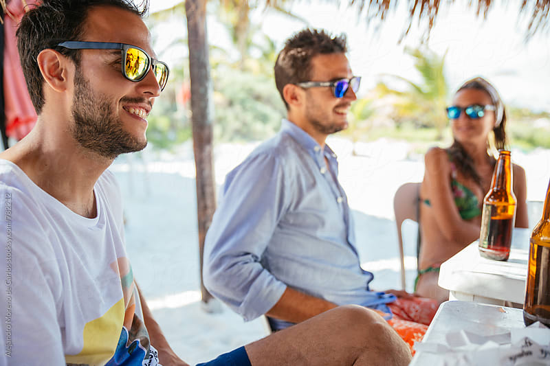 Three friends smiling sitting at a beach bar having a beer by Alejandro Moreno de Carlos for Stocksy United