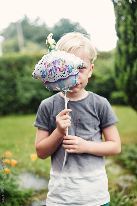 Child holding a happy birthday balloon by sally anscombe for Stocksy United