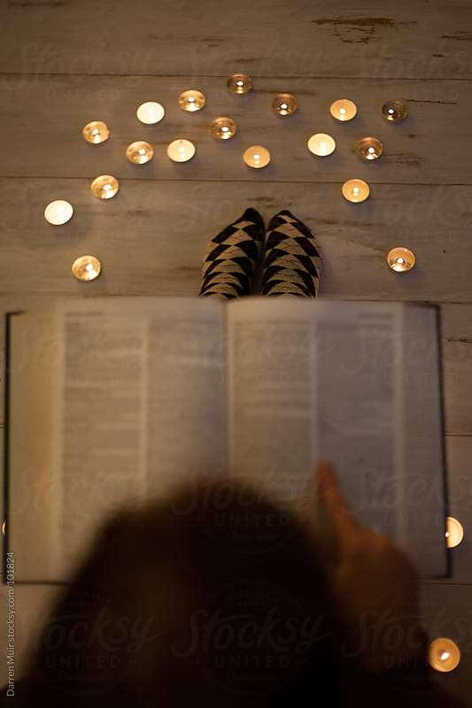 Women reading by candle light. by Darren Muir for Stocksy United