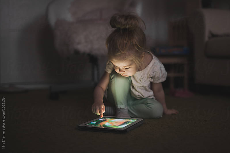 Little girl with tablet in a dark room by Irina Efremova for Stocksy United