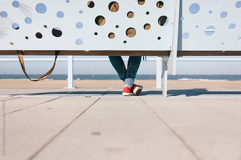Shoes of a woman sitting on a bench. by Koen Meershoek for Stocksy United