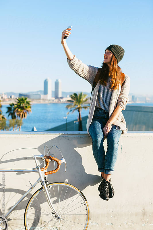 Young woman with her vintage bicycle taking a selfie by the sea. by BONNINSTUDIO for Stocksy United