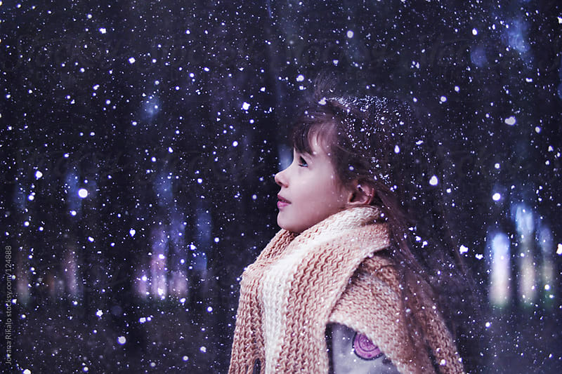 Portrait of a cute little girl watching snow falling by Jovana Rikalo for Stocksy United