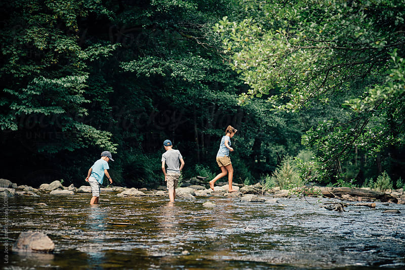 three children walking in a river by Léa Jones for Stocksy United