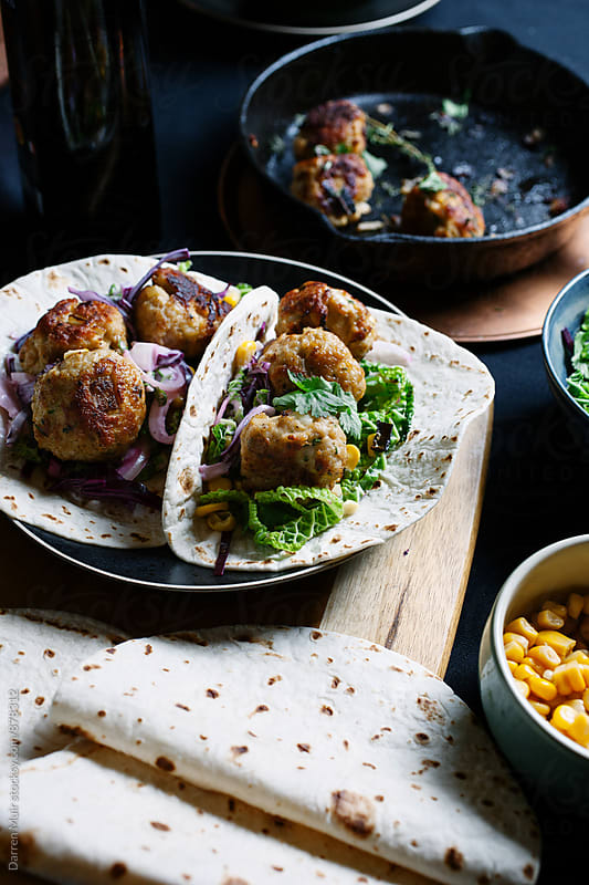 Meatball tacos in a table setting closeup. by Darren Muir for Stocksy United