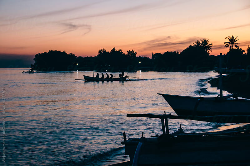 Boats, people and palm trees silhouettes at sunrise, Bali, Indonesia by Alejandro Moreno de Carlos for Stocksy United