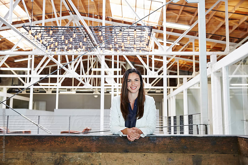 Portrait of millennial Hispanic businesswoman at office by Trinette Reed for Stocksy United