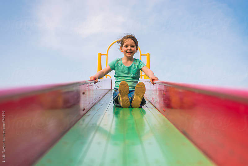 A Young Girl Slides Down The Middle Of A Playground Slide by Leslie Taylor for Stocksy United