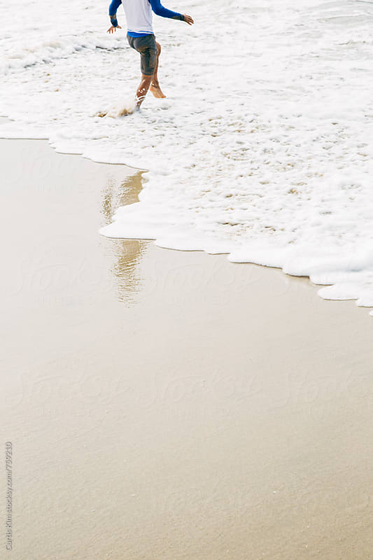 Boy jumping over waves at the beach by Curtis Kim for Stocksy United
