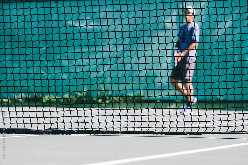 Tennis player seen behind the net in a tennis court playing a match by Inuk Studio for Stocksy United
