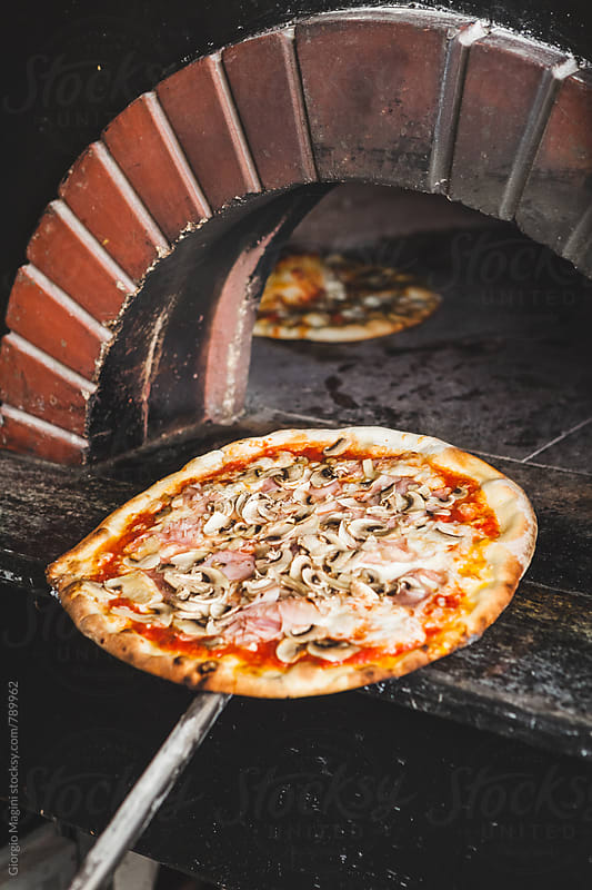 Baked Pizza on a Peel in front of a Wood Oven by Giorgio Magini for Stocksy United