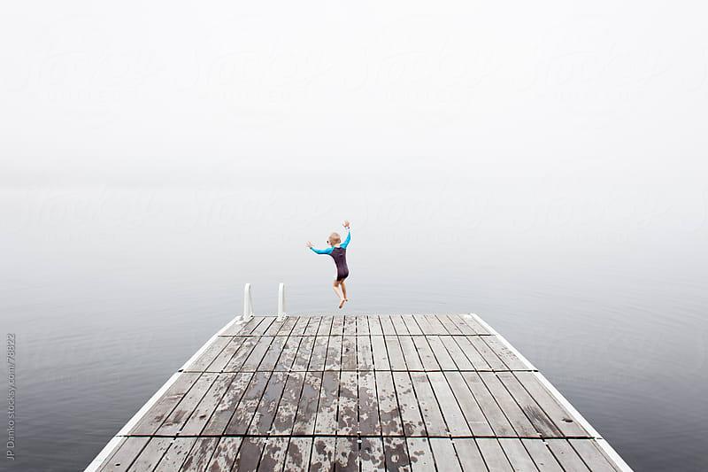Little Boy Jumping off Dock into Misty Lake by JP Danko for Stocksy United