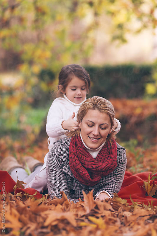 Mother and daughter in autumn park by Dejan Ristovski for Stocksy United