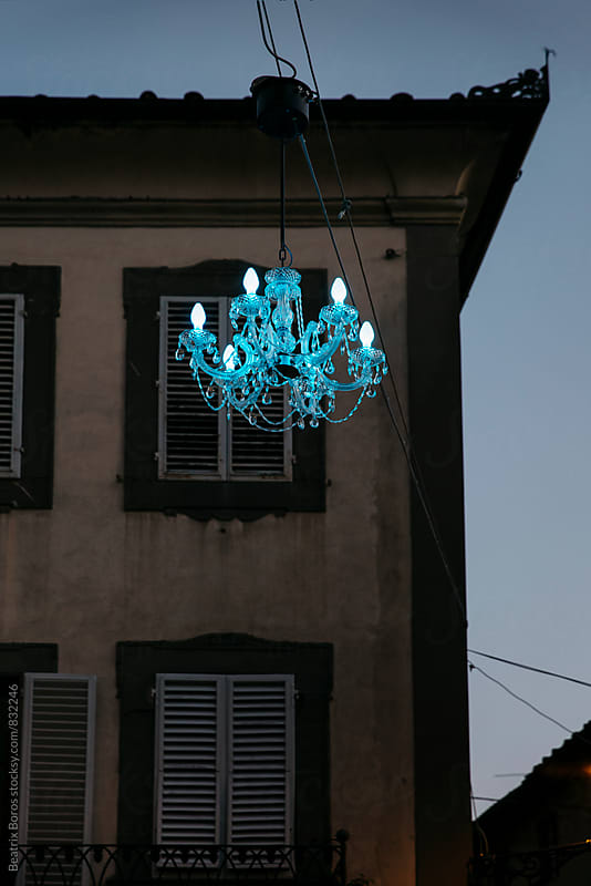 Blue chandelier in front of a building by Beatrix Boros for Stocksy United