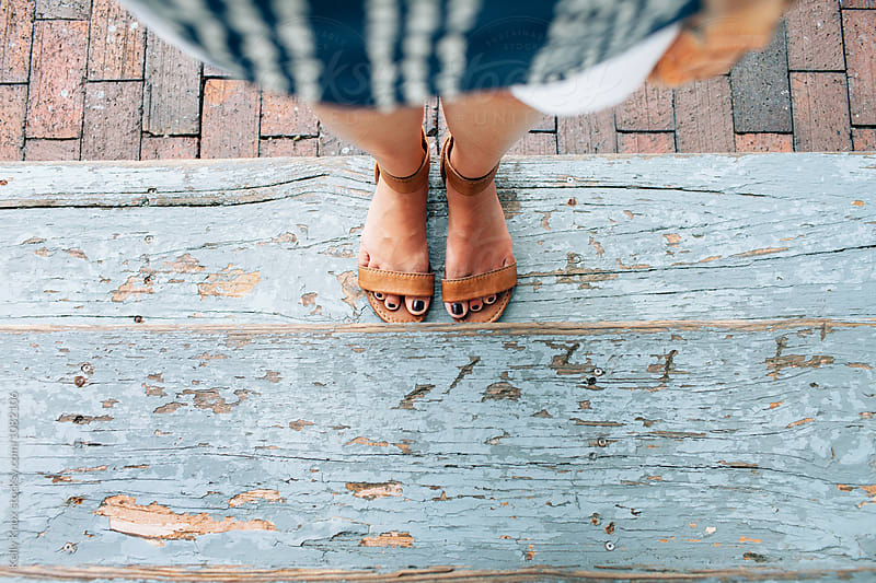 view of woman's feet as she stands on a weathered doorstep by Kelly Knox for Stocksy United
