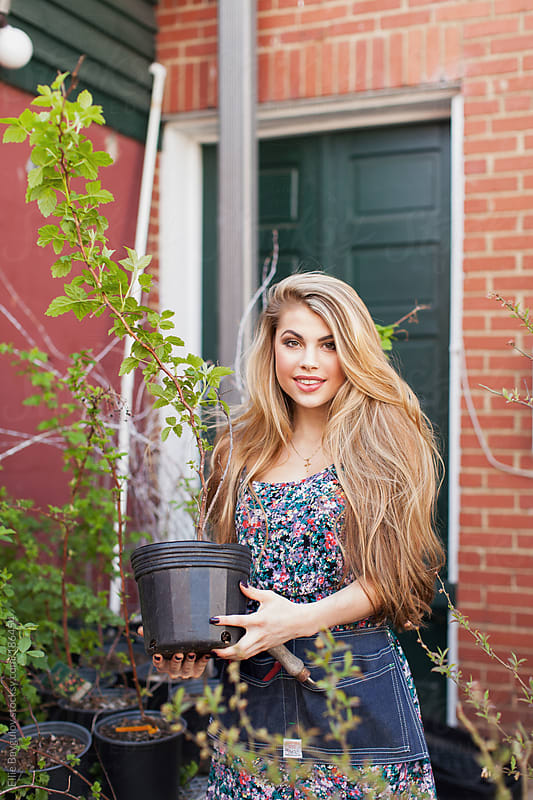 Beautiful blonde girl holding a plant by Ellie Baygulov for Stocksy United