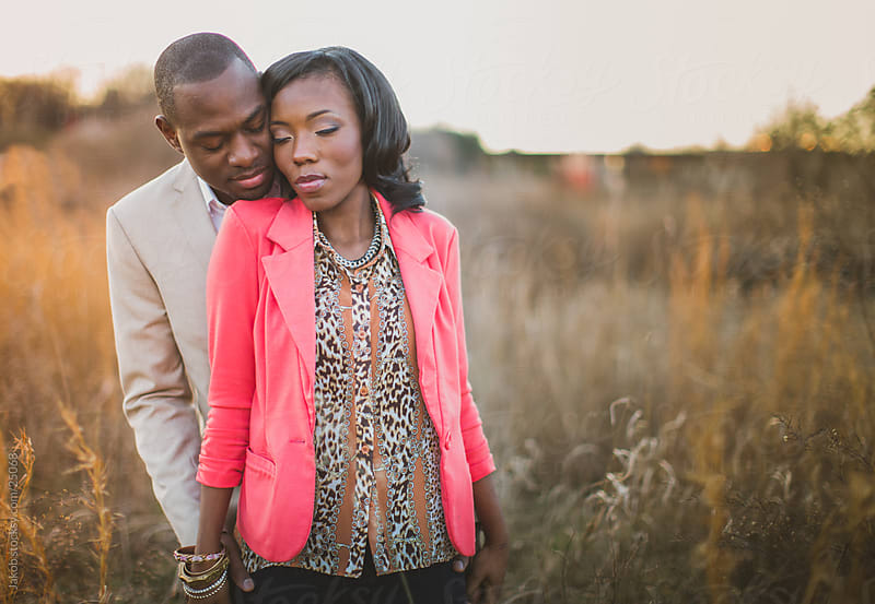 Beautiful african-american couple standing in a field by Jakob for Stocksy United