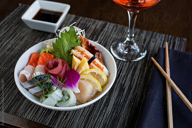Chirashi bowl with cocktail and chopsticks by Andrew Cebulka for Stocksy United
