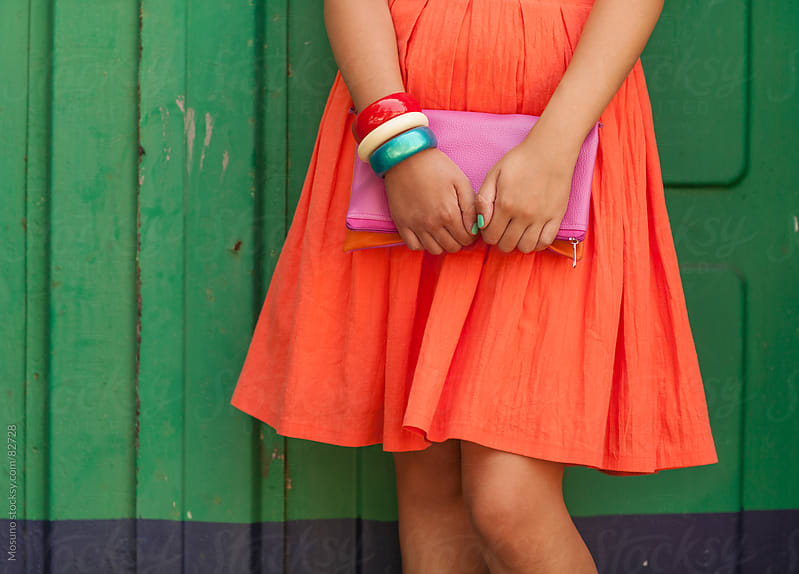 Woman in an orange dress standing against green wall. by Mosuno for Stocksy United