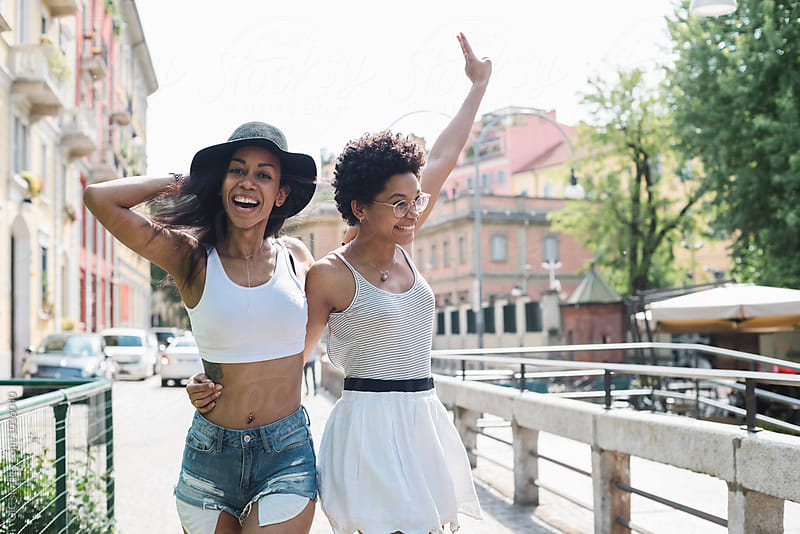 Happy girl friends having fun outdoors together by Simone Becchetti for Stocksy United