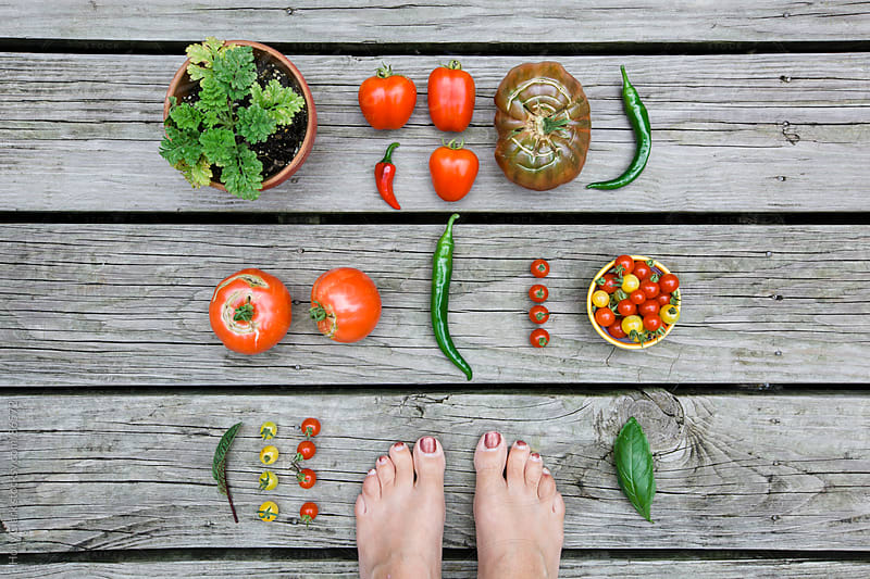 Looking down on a woman's feet surrounded by a garden harvest on a wooden background. by Holly Clark for Stocksy United