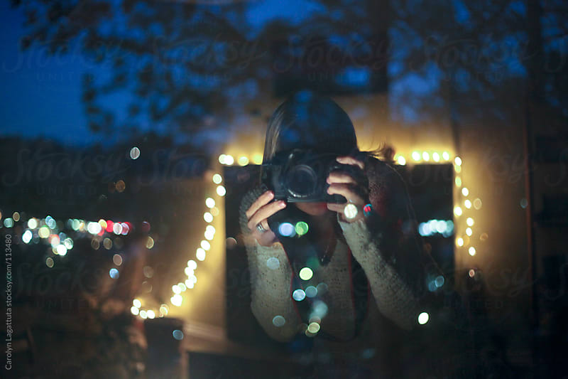 Girl taking a photo of herself in the reflection of the window by Carolyn Lagattuta for Stocksy United