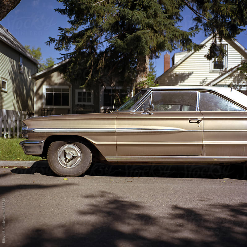 An old classic car parked along a residential street. by Riley J.B. for Stocksy United