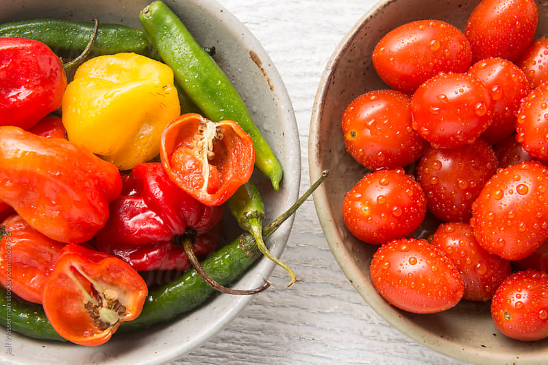 Jalapeno and Other Hot Peppers with bowl of Cherry Tomatoes by Jeff Wasserman for Stocksy United