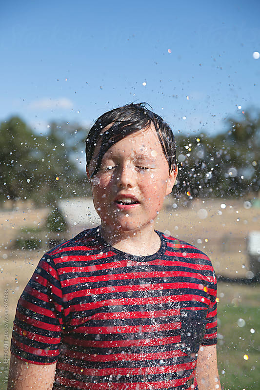 A young boy on a farm during summer getting sprayed with water by Natalie JEFFCOTT for Stocksy United