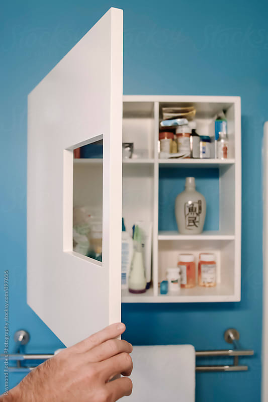 Man opening Medicine Cabinet by Raymond Forbes LLC for Stocksy United