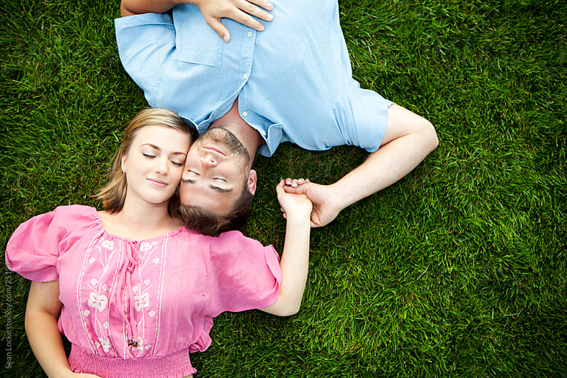 Grass: Cute Couple Naps Together Holding Hands by Sean Locke for Stocksy United