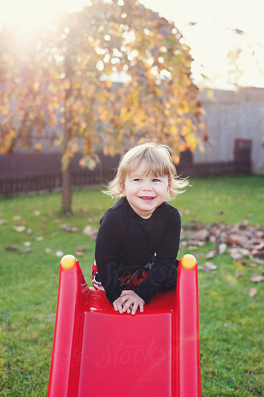 Little girl on top of a red slide smiling and looking happy by Lea Csontos for Stocksy United