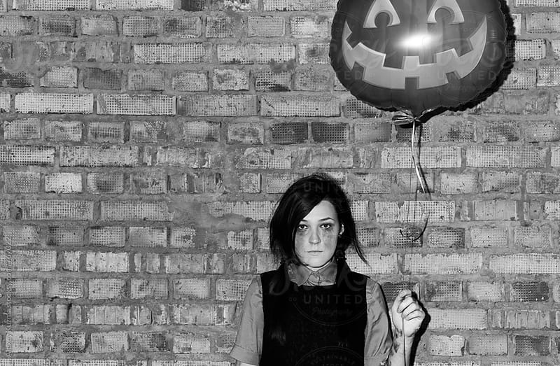 halloween portrait of young gothic woman holding Halloween Party Balloon by Alexey Kuzma for Stocksy United