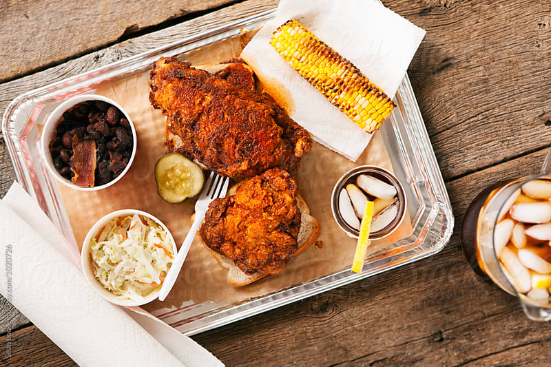 Fried: Nashville Hot Chicken Breast And Thigh On Meal Tray With Sides And Tea by Sean Locke for Stocksy United