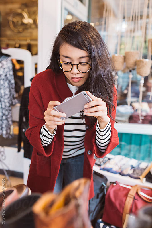 Urban woman taking pictures with her phone in local downtown shop by Carey Shaw for Stocksy United