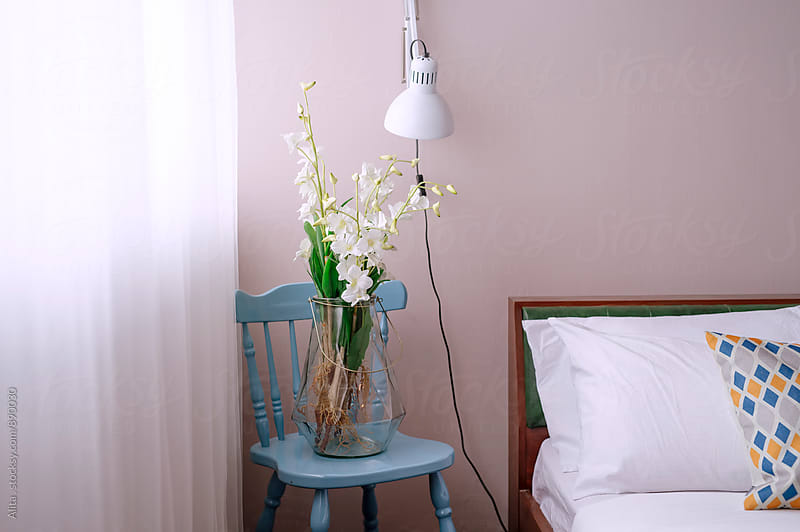 Beautiful orchids on bed side by Alita Ong for Stocksy United