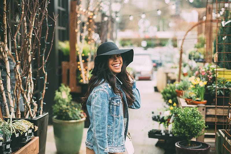 Smiling Young Woman In Plant Nursery by Luke Mattson for Stocksy United