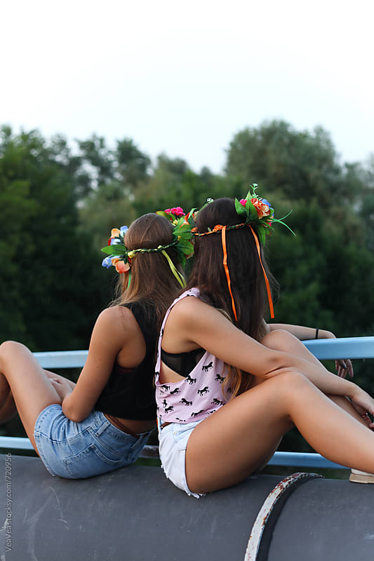Two attractive woman sitting on the bridge from the back  by Marija Mandic for Stocksy United