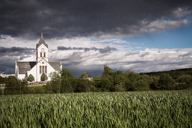 Epic stormy sky above a scandinavian church by green field by Lior + Lone for Stocksy United