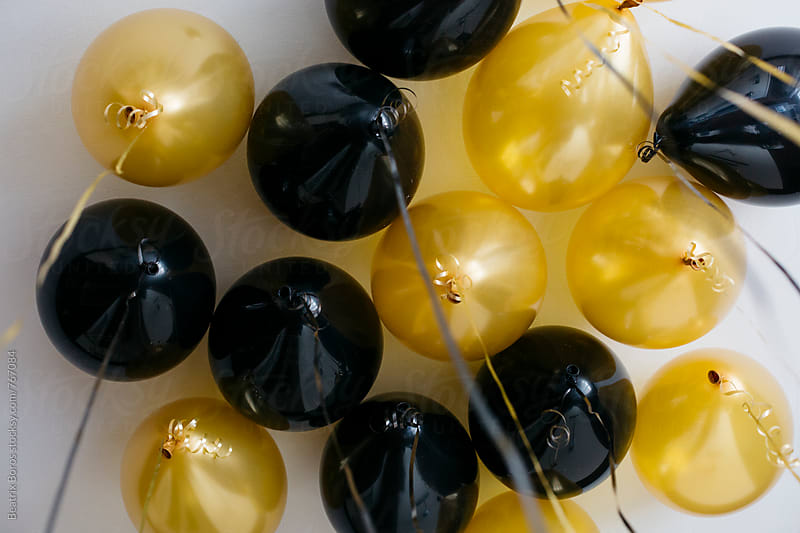 Black and golden yellowish ballons on the ceiling by Beatrix Boros for Stocksy United