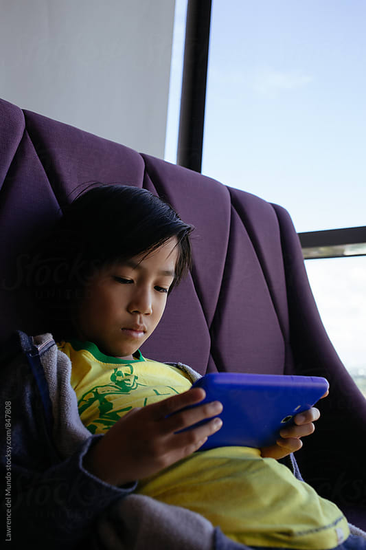 Young boy busy playing with a tablet by Lawrence del Mundo for Stocksy United
