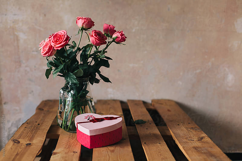 Bouquet of roses and a Valentine gift on a table  by Marija Mandic for Stocksy United