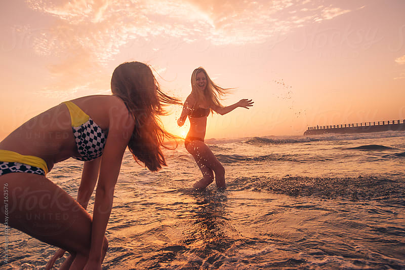 Friends having fun swimming in the sea at sunrise by Aila Images for Stocksy United