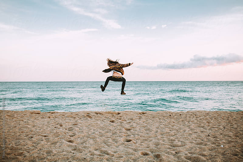 man jumping on the beach by Thais Ramos Varela for Stocksy United